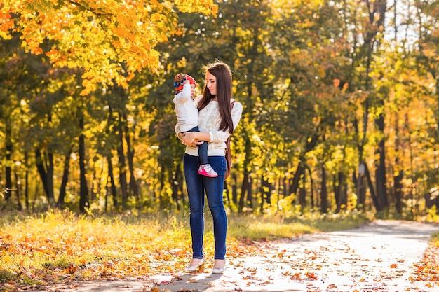 젊은 어머니와 그녀의 유아 소녀는 가을에 재미가 있습니다.