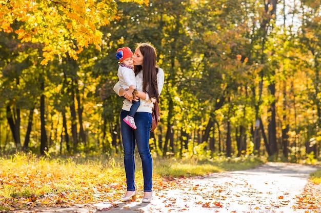 若い母親と彼女の幼児の女の子は秋に楽しんでいます