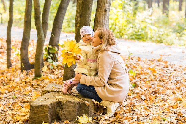 Молодая мама и ее малышка веселятся осенью
