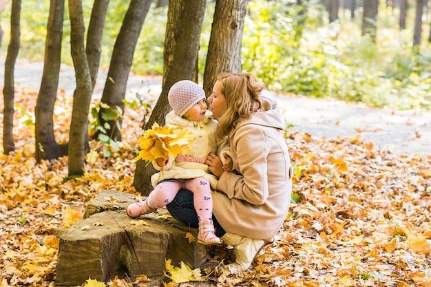젊은 어머니와 그녀의 유아 소녀는 가을에 재미를