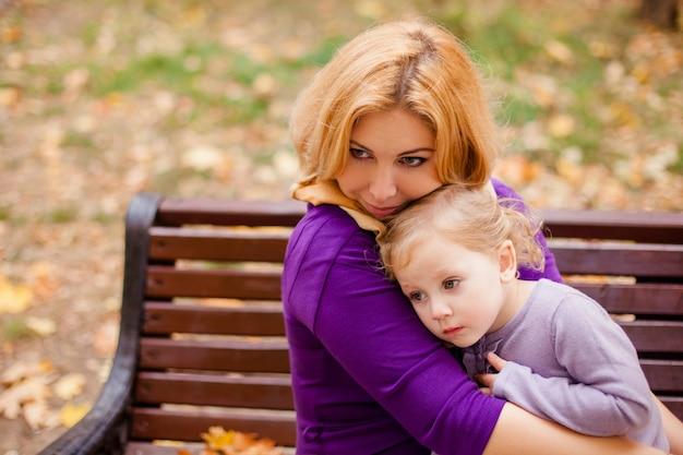 若い母親と秋に楽しんで彼女の幼児の女の子