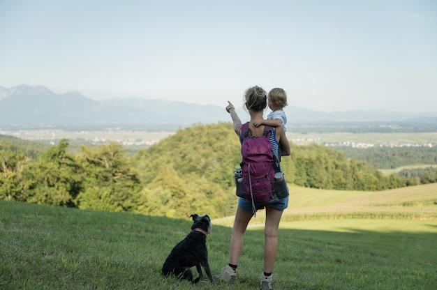 Молодая мать и ее малыш, глядя на прекрасный вид на холмы