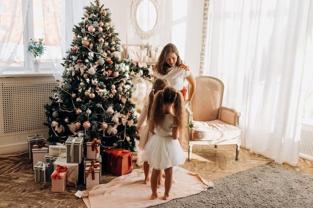 Молодая мама и две ее очаровательные дочки в красивых платьях стоят у новогодней елки с подарками в светлой уютной комнате.