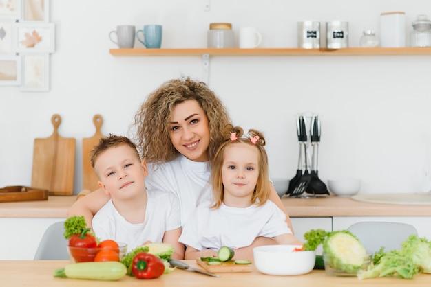 젊은 어머니와 그녀의 두 아이 야채 샐러드 만들기