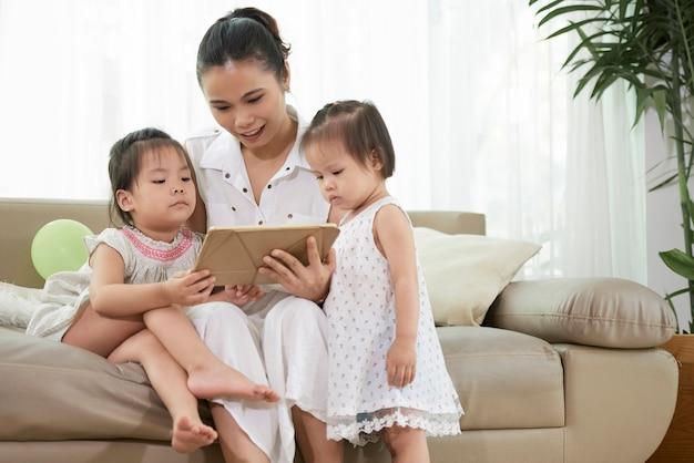 自宅のタブレットコンピューターでアニメを見ている若い母親と彼女の2人の幼い娘