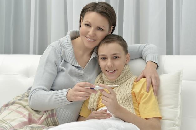 ベッドで若い母親と病気の息子