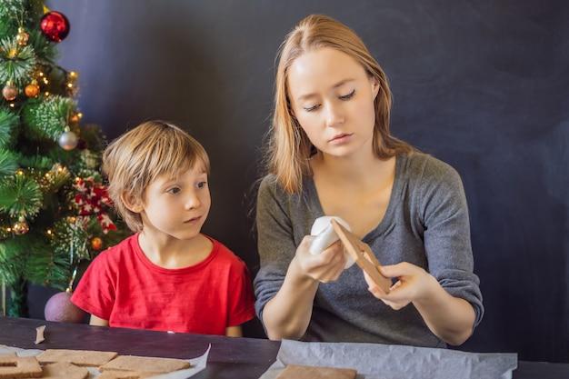 Молодая мать и ребенок делают пряничный домик