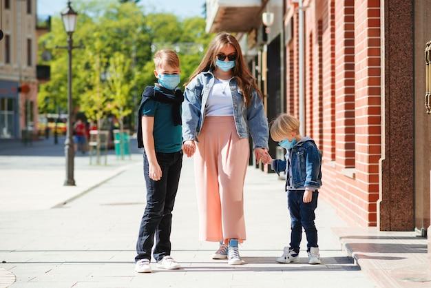 コロナウイルスの流行中に散歩に若い母親と子供。医療マスクを身に着けている家族。