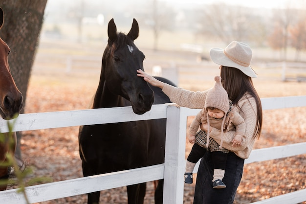 Молодая мать и маленькая девочка возле лошадей в осенний солнечный день