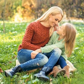 若い母親と幼い娘が屋外で抱き合っています。
