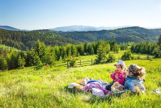 Молодая мама и маленькие дочери лежат на поросшем травой склоне или любуются шикарным видом лисы, растущей на холмах.