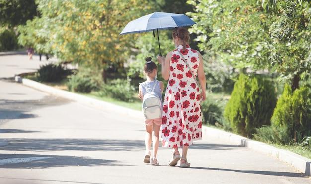 Молодая мать и маленькая девочка в парке.