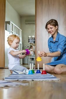 어린 엄마와 어린 아이가 집에서 유치한 다채로운 핸드 벨 음악 소리를 연주