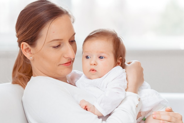 若い母親と白い寝室で生まれたばかりの赤ちゃん