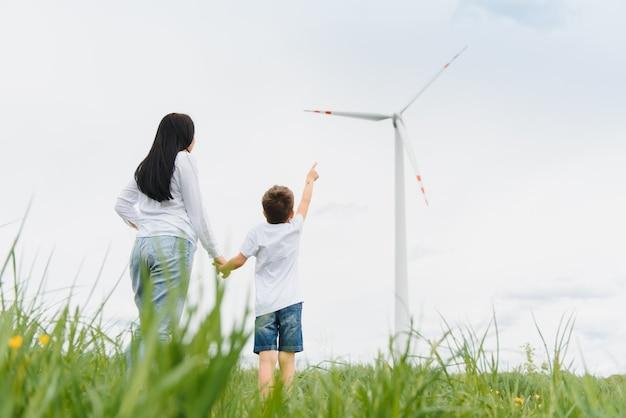 Молодая мать и сын на ветряной электростанции