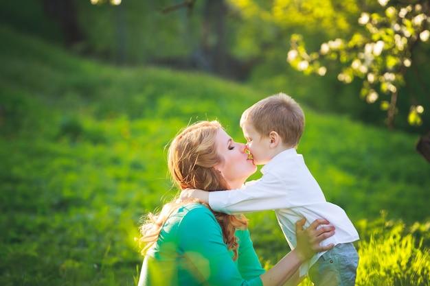 Молодая мать и сын на прогулке в летнем парке
