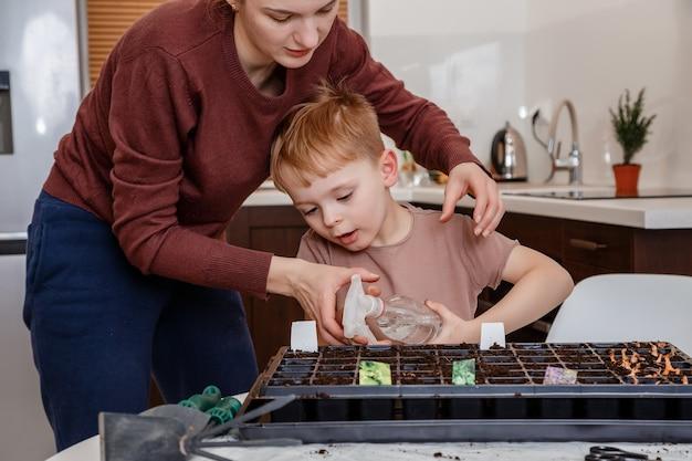 Молодая мать и сын играют с грязью, подготовленной для семян.