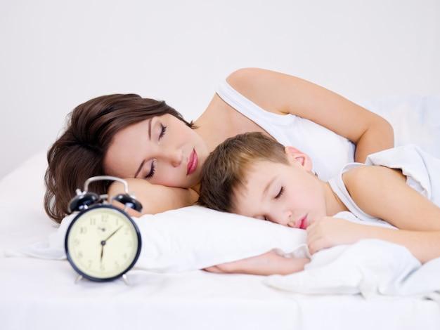 Молодая мать и сын спят на кровати. ì настольные часы на переднем плане