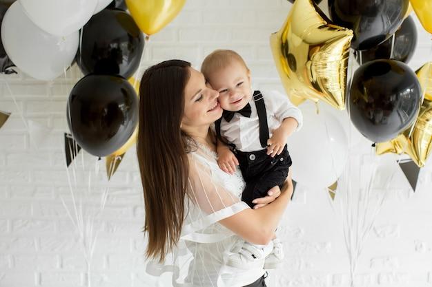 Молодая мать и сын с воздушными шарами. день рождения