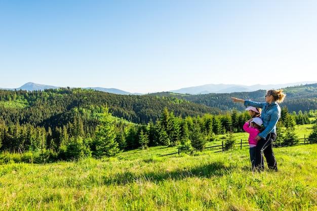Молодая мама и две маленькие дочери-путешественники стоят на склоне холма с великолепным видом на холмы, покрытые густым еловым лесом, на фоне голубого неба в солнечный теплый летний день