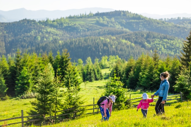 Молодая мама и две маленькие дочери путешественники стоят на склоне холма, откуда открывается шикарный вид на холмы, покрытые густым еловым лесом, на фоне голубого неба.