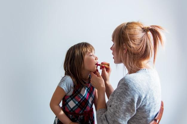 小さな娘に口紅を塗る若い母親 Premium写真