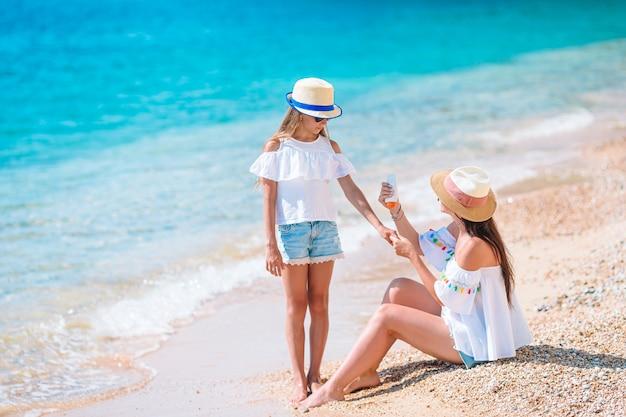 ビーチで娘の鼻に日焼け止めクリームを適用する若い母親。日焼け止め