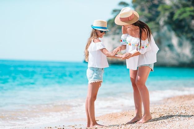 若い母親がビーチで娘の鼻に日焼け止めを適用します。