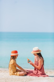 ビーチで娘の鼻に日焼け止めを適用する若い母親