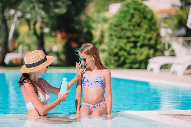 若い母親が娘の鼻に日焼け止めを適用します。