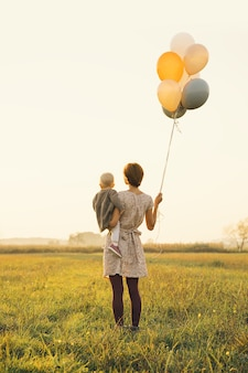 Young mother and baby girl with balloons in sunlight at sunset on nature outdoors