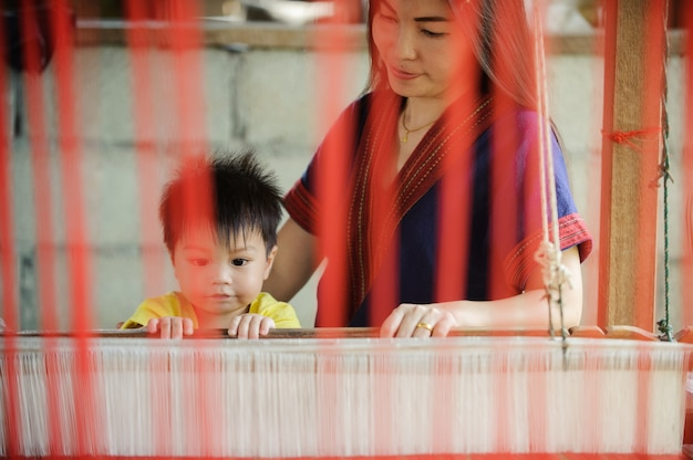 Young mother and baby local wovening thai silk clothat