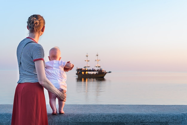 Young mother and baby looking at sea and ship. vacation at sea with children