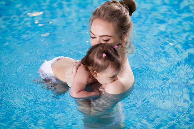 Young mother bathes the baby in the pool.