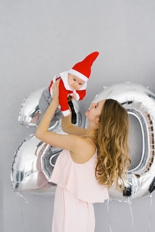 A young mother in a beautiful pink dress holds her baby son in a little santa costume on the   of figures from 20 foil balloons