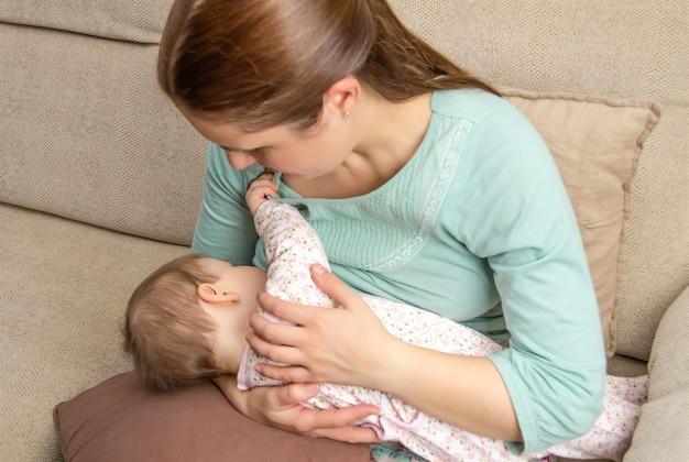 집에서 아기에게 모유 수유를 하는 젊은 엄마