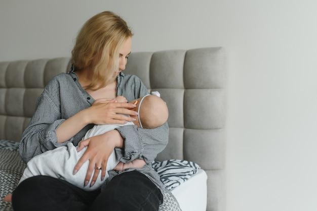 Молодая мать кормит своего новорожденного ребенка грудью дома