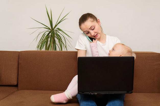若い母親のビジネスウーマン、赤ちゃんを抱いて仕事をし、電話で話している。