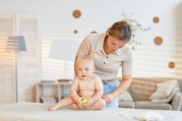 Молодая мать переодевает своего маленького сына, который сидит на столе с зеленым яблоком