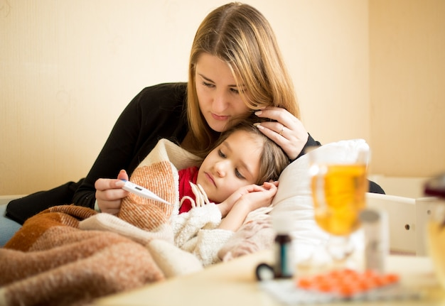 ベッドで横になっている病気の娘の体温をチェックする若い母親
