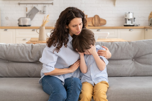 Young mother comforts crying son