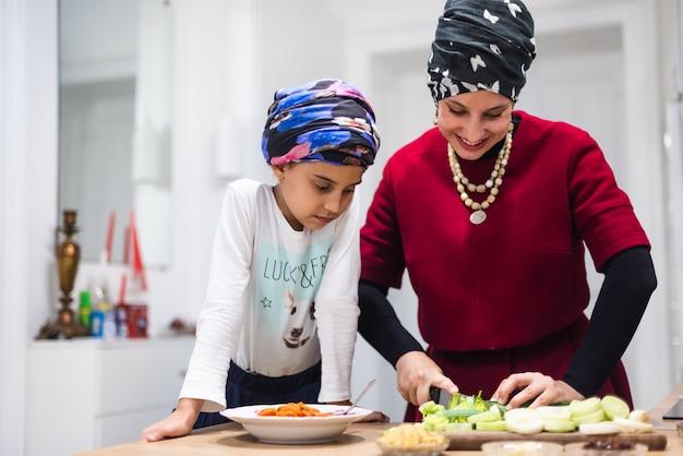 若い母親が幼い娘と夕食を作り、幸せな母性、赤ちゃんに野菜を見せて