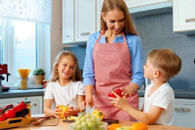 Молодая мать готовит с детьми на кухне