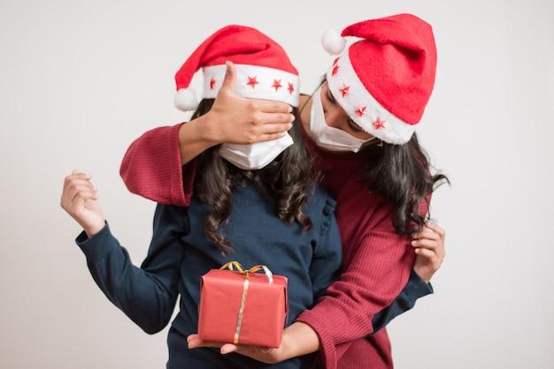 Молодая мать закрыла глаза своей дочери, дающей красный подарок на рождество.