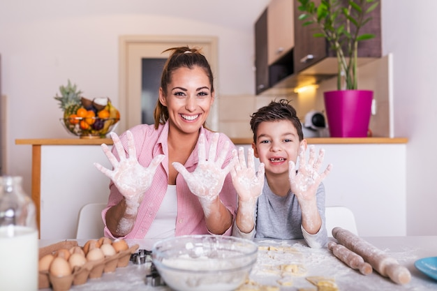 Young mother and cute little son boy preparing the dough, bake cookies and having fun in the kitchen. happy family are preparing bakery together.
