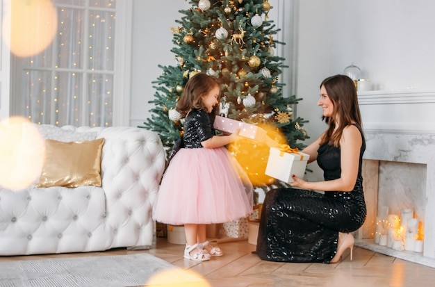 Young mother and daughter in evening dresses give each other gifts on  of christmas tree