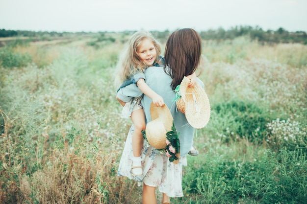 The young mother and daughter on green grass space