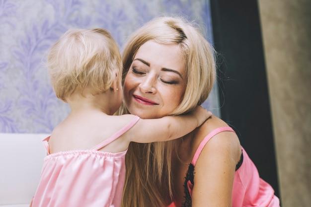 침실에 있는 어린 엄마 딸 작은 아기가 함께 껴안고 행복합니다.