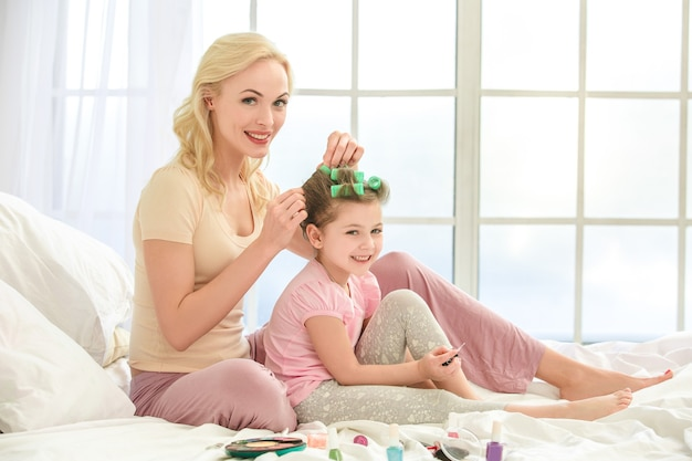 Young mother and daughter morning on bed indoors