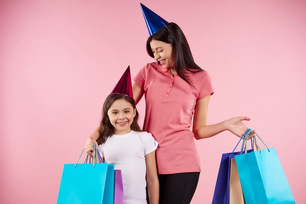 Young mother and daughter in party caps